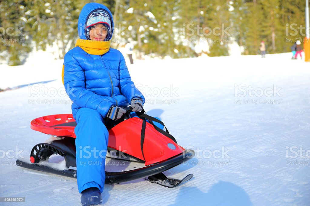 Little boy and his sled in winter stock photo