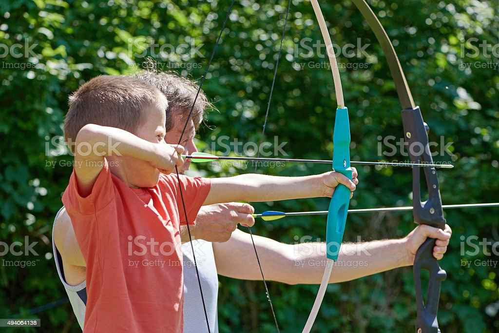 Little boy and man with big bow shooting stock photo