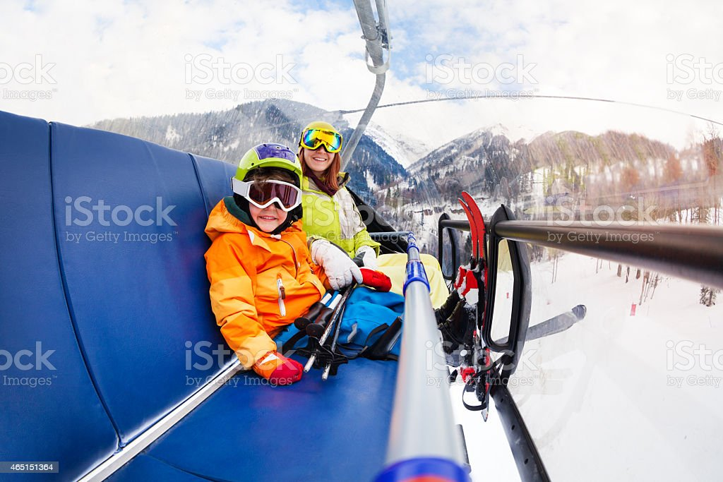 Little boy and mother on ski lift chair stock photo