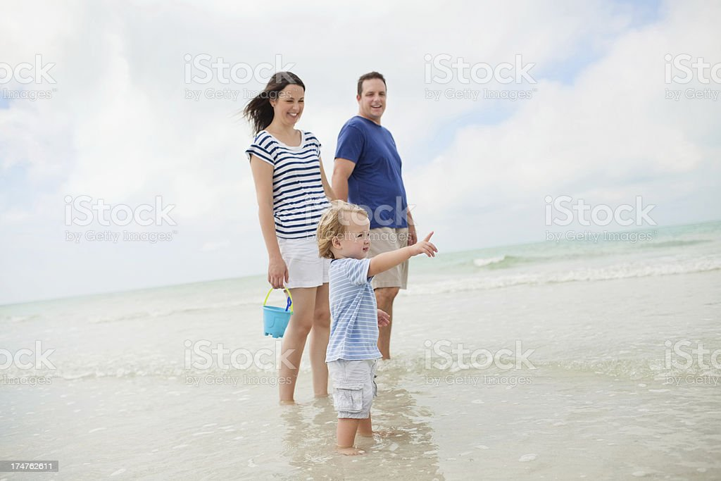 Little Boy And Parents Standing In Water At Beach royalty-free stock photo