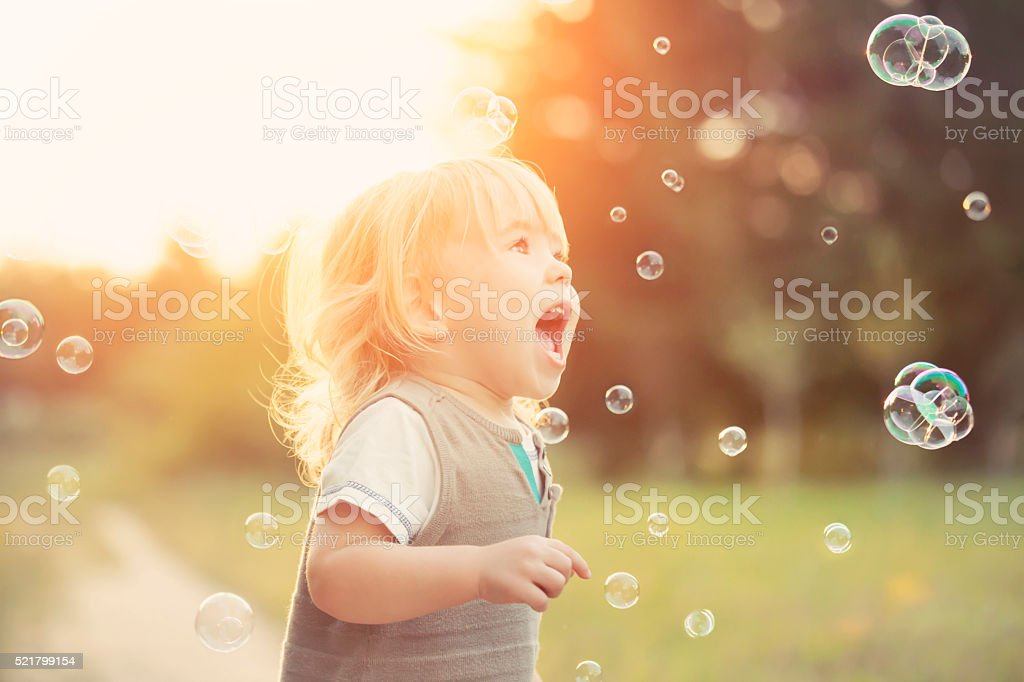 Little boy and soap bubbles stock photo