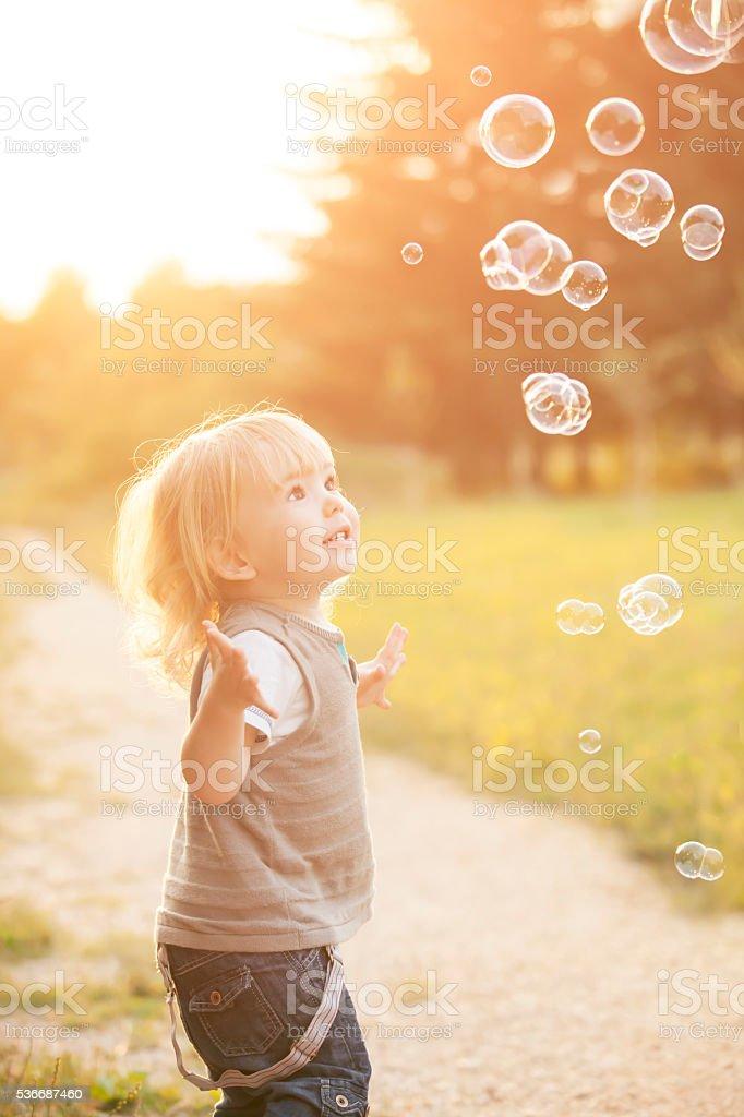 Little boy and soap bubbles stock photo
