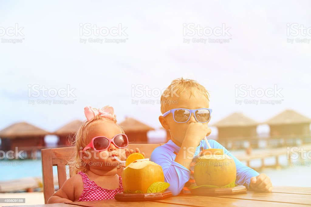 little boy and toddler girl drinking coconut cocktail on beach stock photo