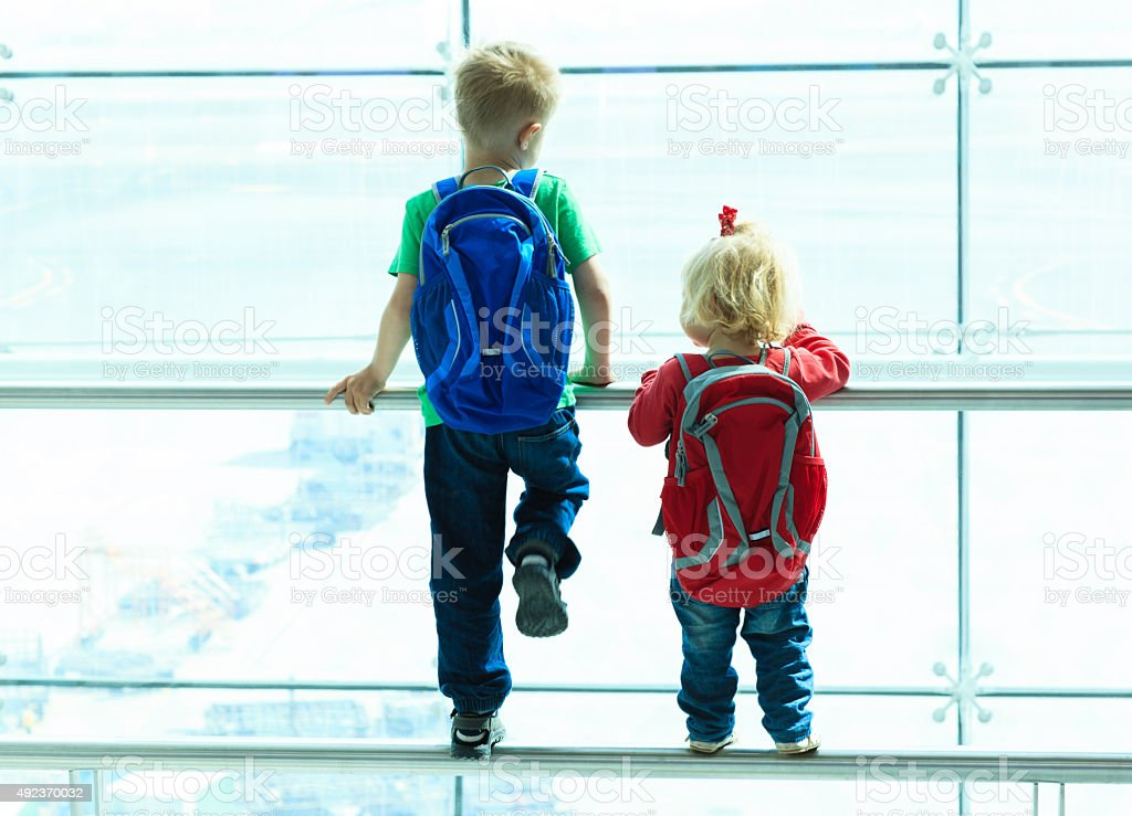 little boy and toddler girl in the airport stock photo
