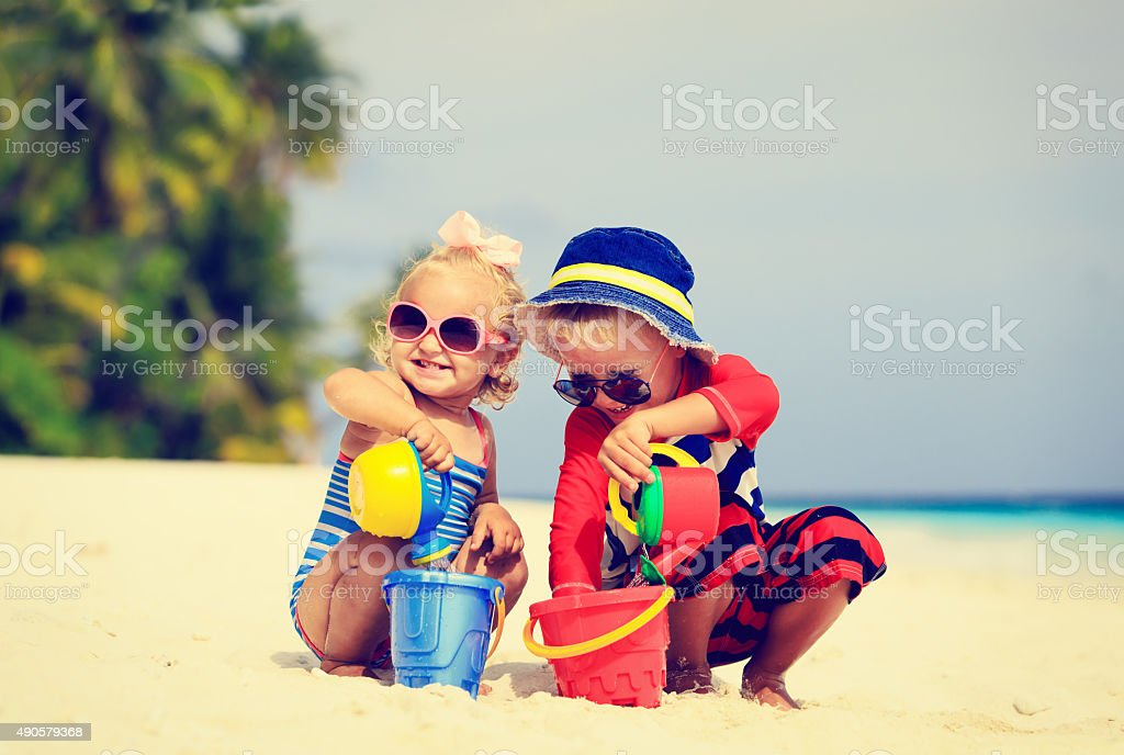 little boy and toddler girl play with sand on beach stock photo