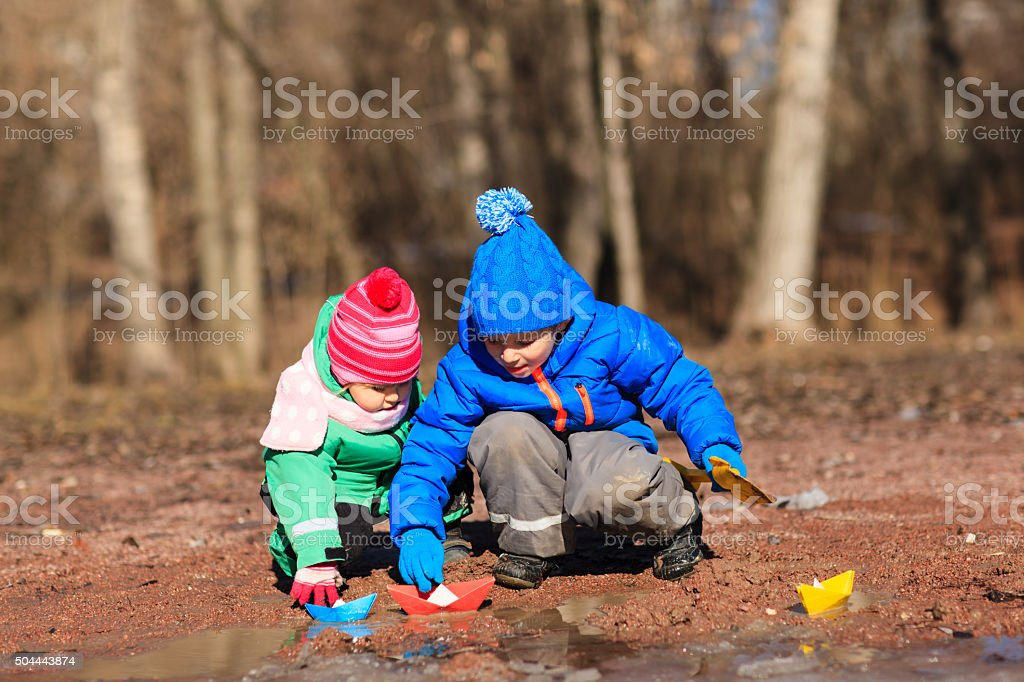 little boy and toddler girl playing with water in spring stock photo