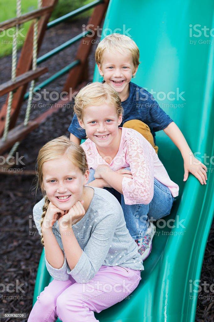 Little boy and two girls on playground slide stock photo