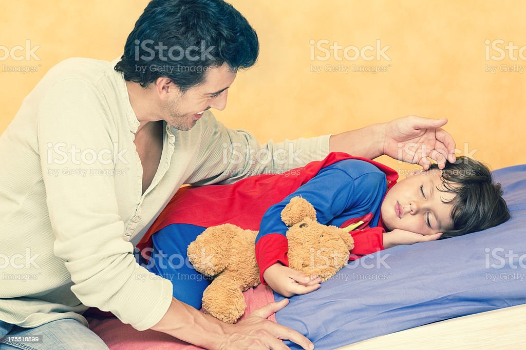 little boy as superman sleeping in his bed royalty-free stock photo