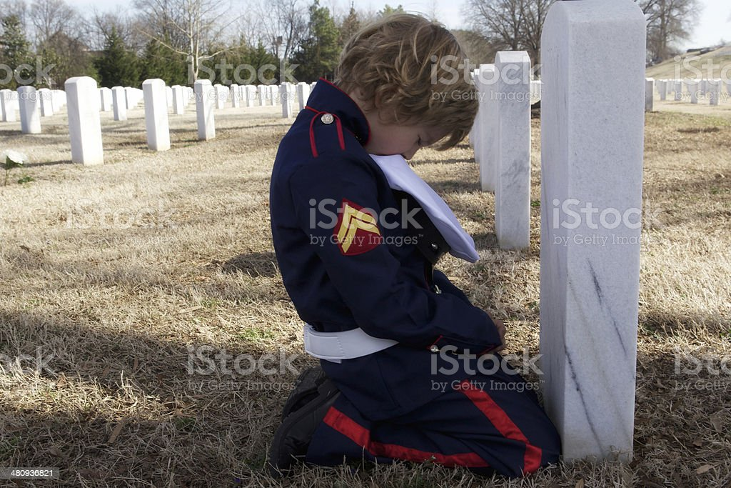 Little Boy At Dad's Grave Site stock photo