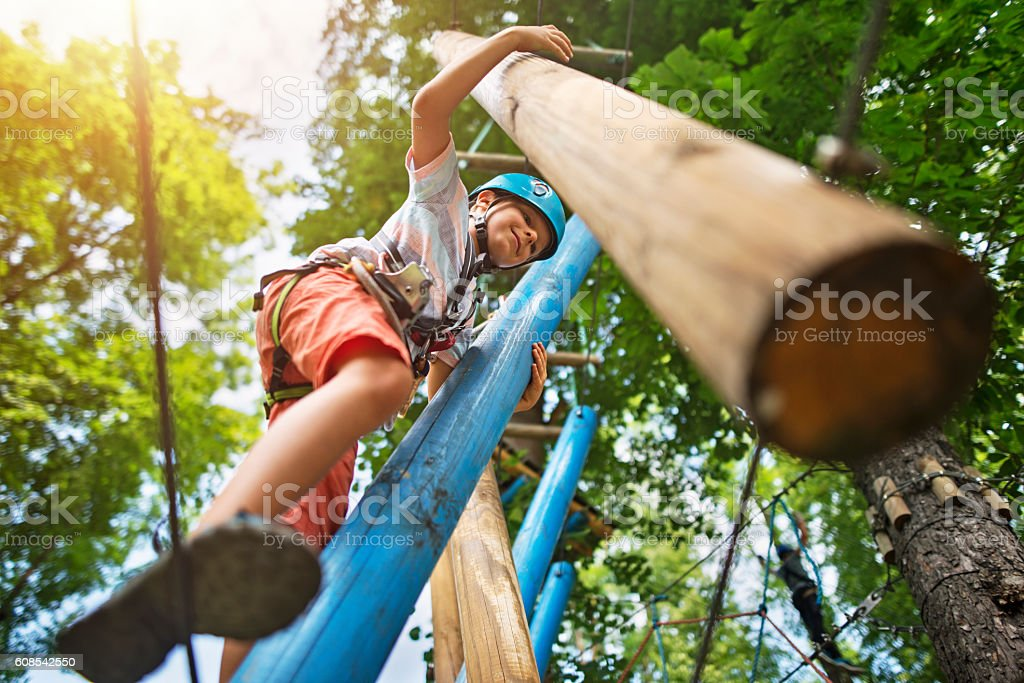 Little boy at outdoors ropes course obstacle stock photo