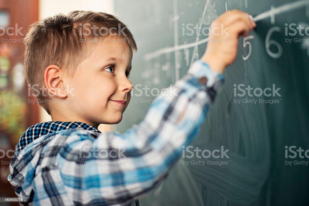 Little boy at school in math class stock photo