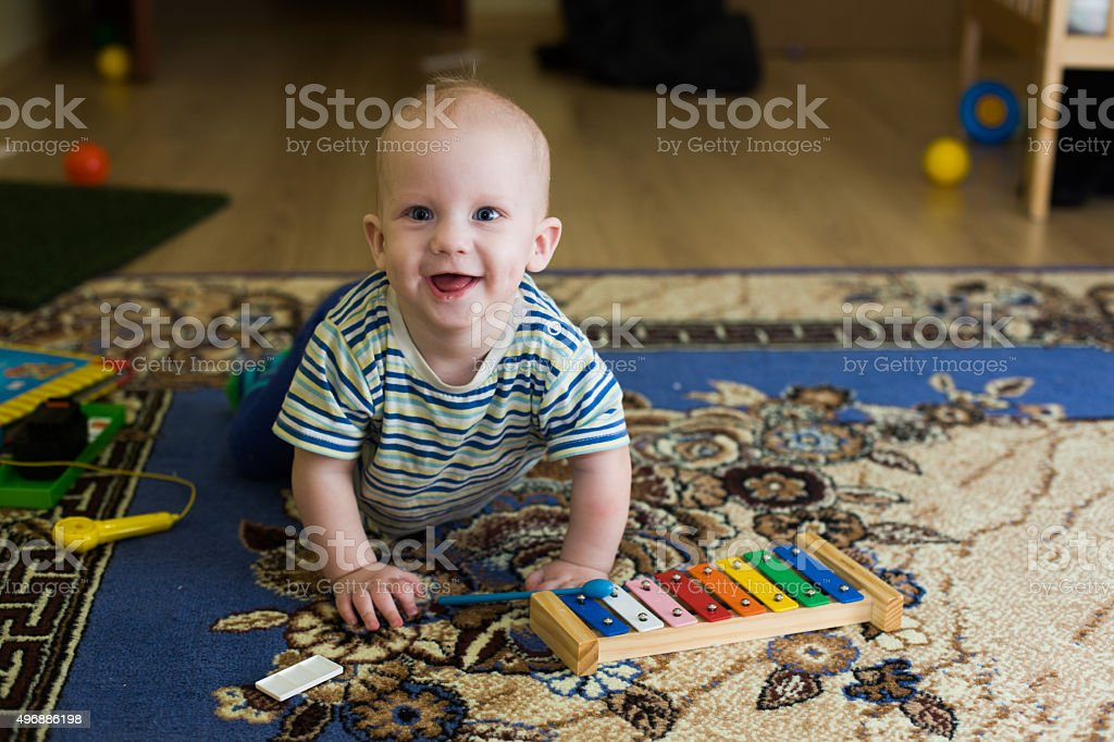 little boy, baby, xylophone musical instrument, fun rejoices at home stock photo