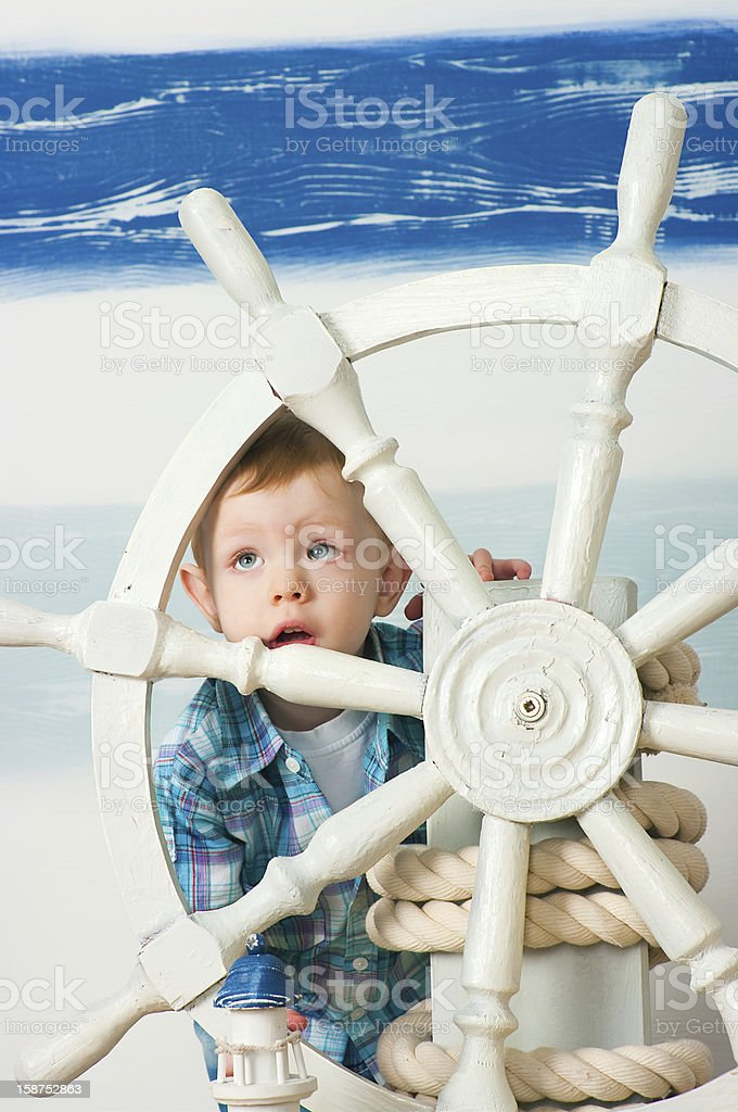 little boy behind a ship steering wheel royalty-free stock photo