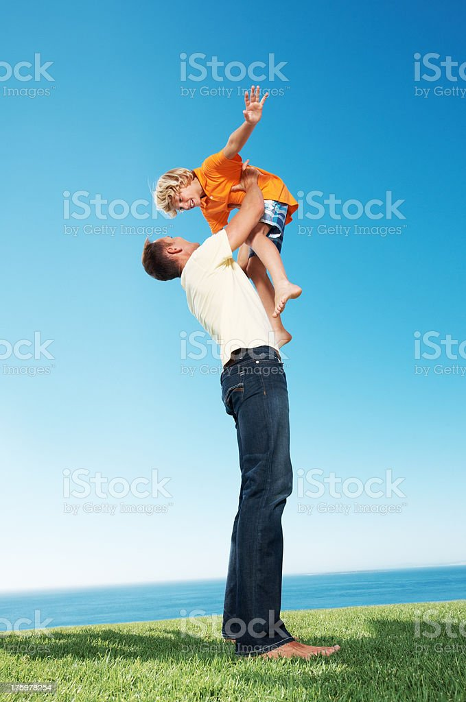 Little boy being lifted up by his father stock photo