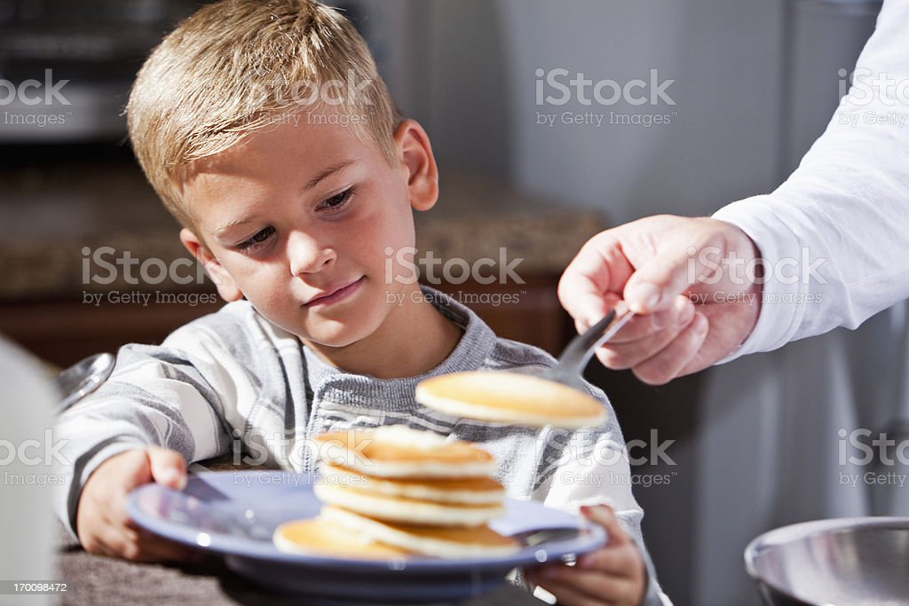 Little boy being served pancakes for breakfast royalty-free stock photo