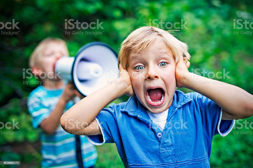 Little boy being yelled on by his brother stock photo