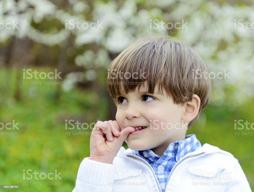 little boy biting finger stock photo