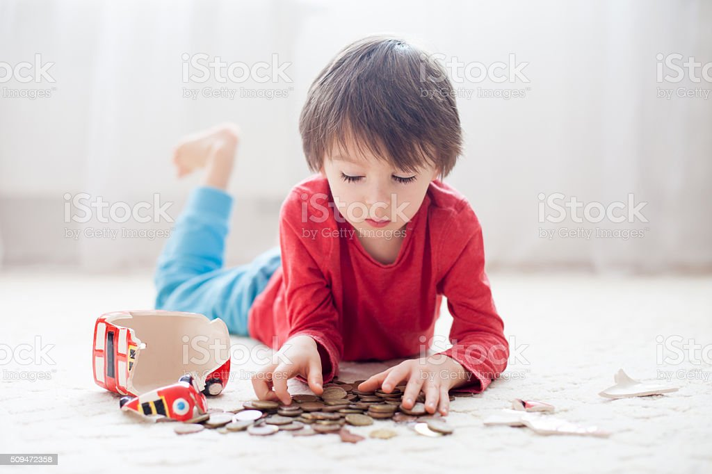 Little boy, breaking his piggy bank to buy gift stock photo