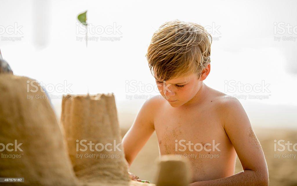 Little Boy Building a Sandcastle stock photo