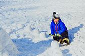 little boy building castle from snow