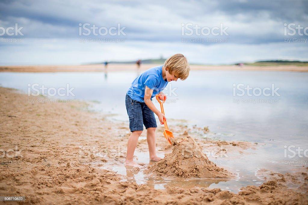 Little boy building sand castle stock photo