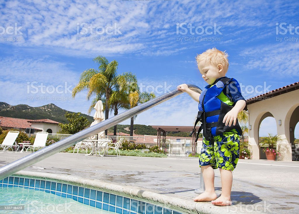 Little Boy Cautiously Stepping into Outdoor Pool stock photo