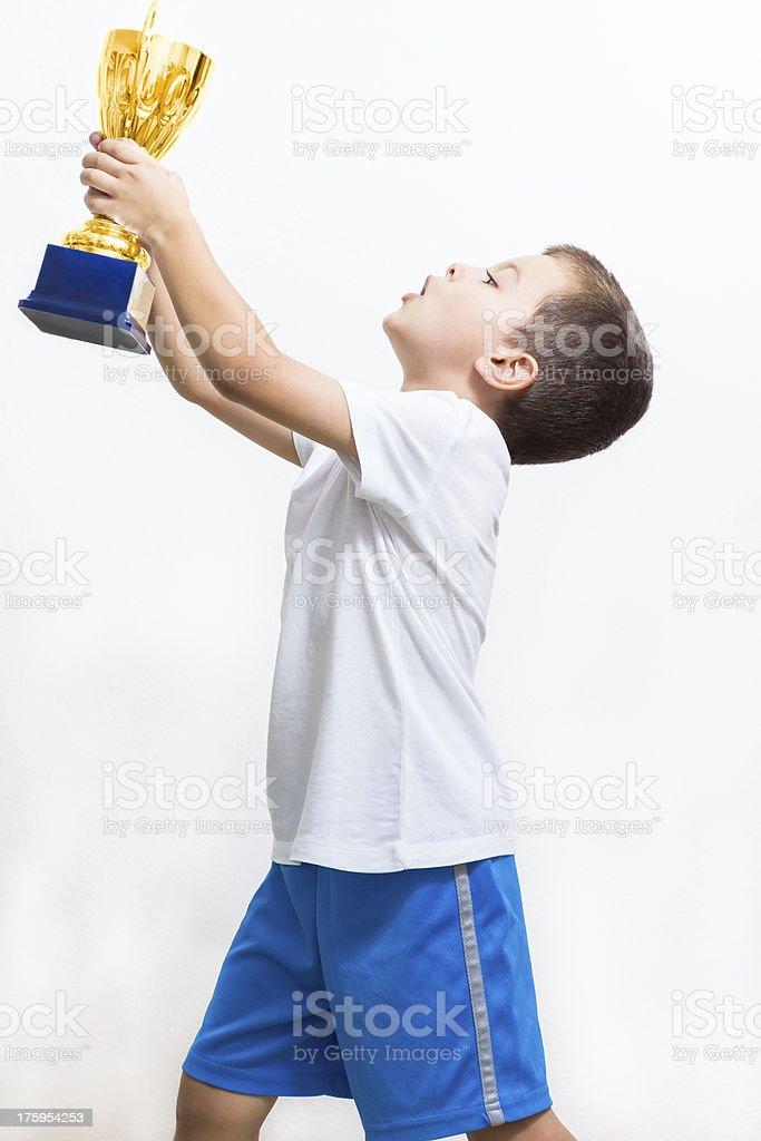 Little boy celebrates his golden trophy royalty-free stock photo