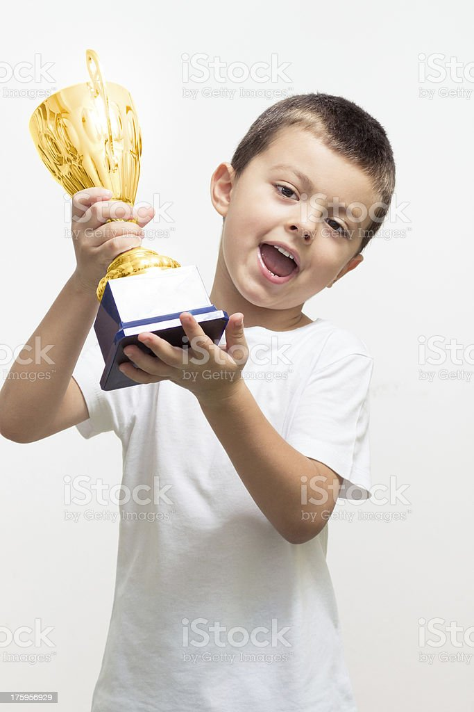 Little boy celebrates his golden trophy royalty-free stock photo