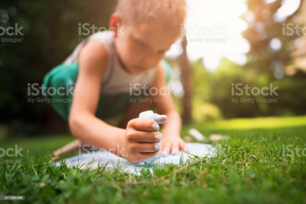 Little boy chalking in the garden stock photo