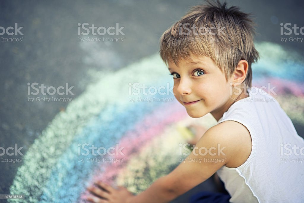 Little boy chalking rainbow stock photo