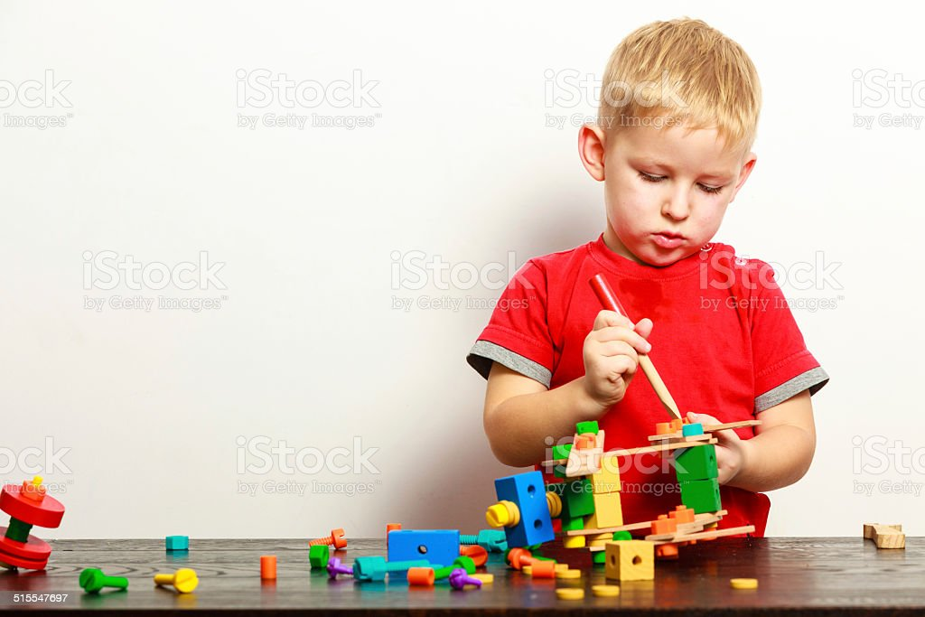 Little boy child playing with building blocks toys interior. stock photo