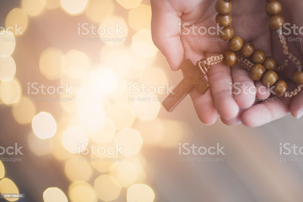 Little boy child praying and holding wooden rosary. stock photo