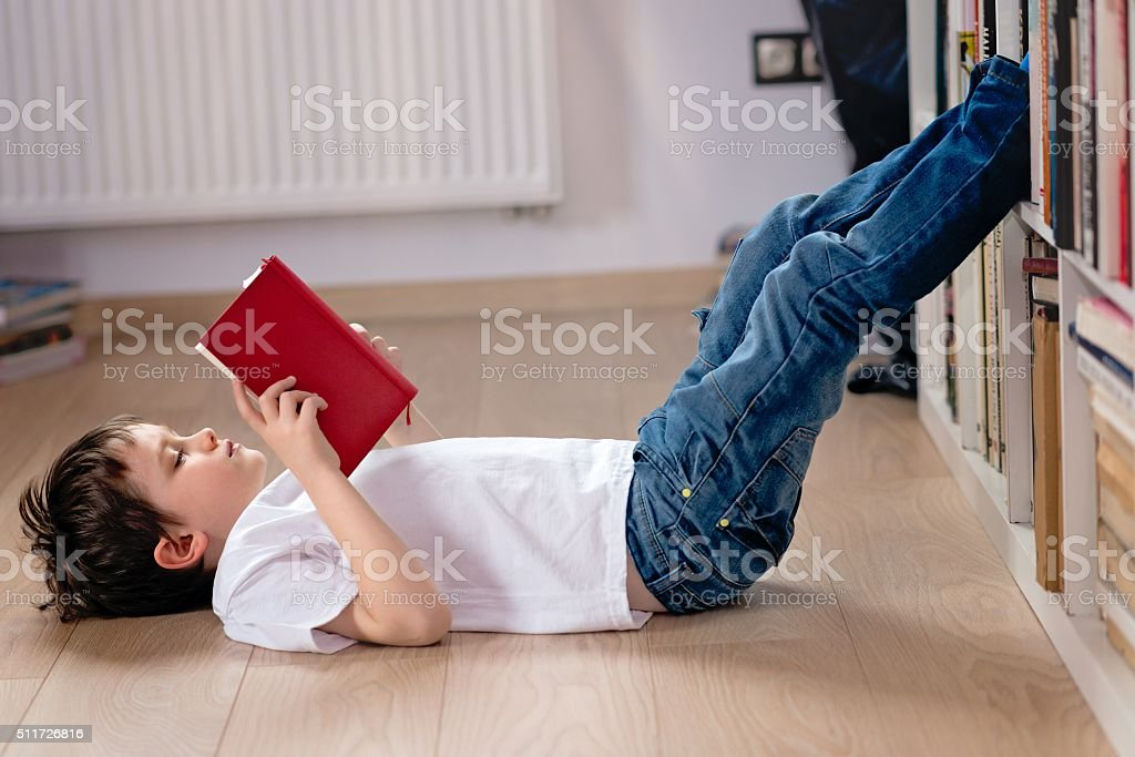 Little boy child reading a book in the library. stock photo