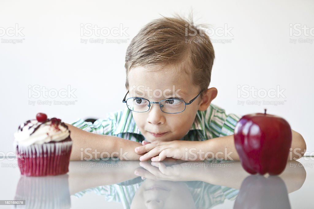 Little boy choosing between a cupcake and apple stock photo