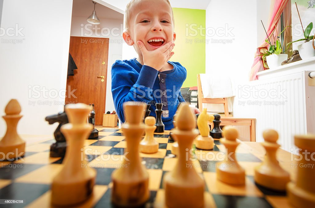 Little boy clever child playing chess thinking, stock photo