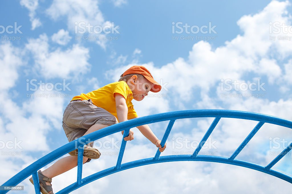 little boy climbs up the ladder on the playground stock photo