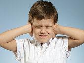 little Boy closing his ears
