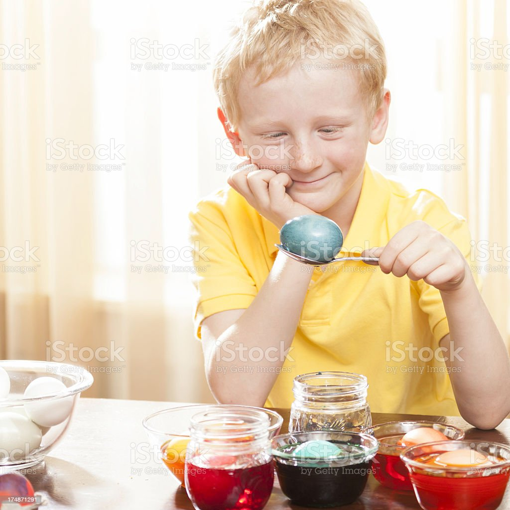 Little Boy coloring Easter eggs royalty-free stock photo
