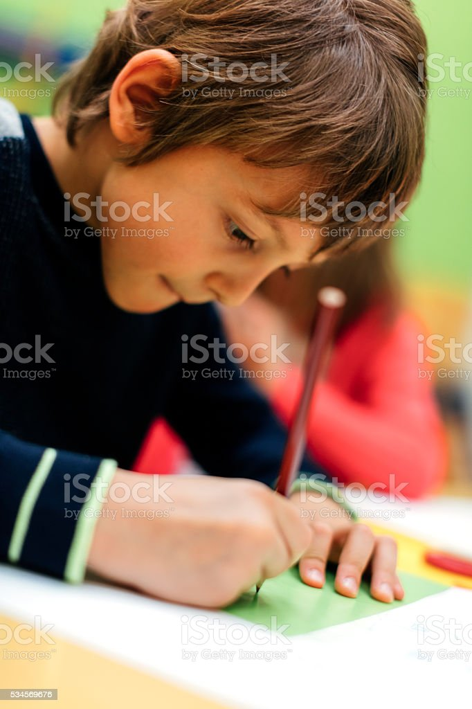 Little Boy coloring In his Kindergarten stock photo