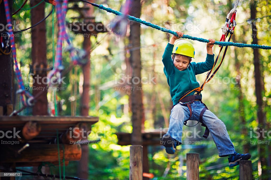 Little boy completing ropes course in outdoors adventure park stock photo