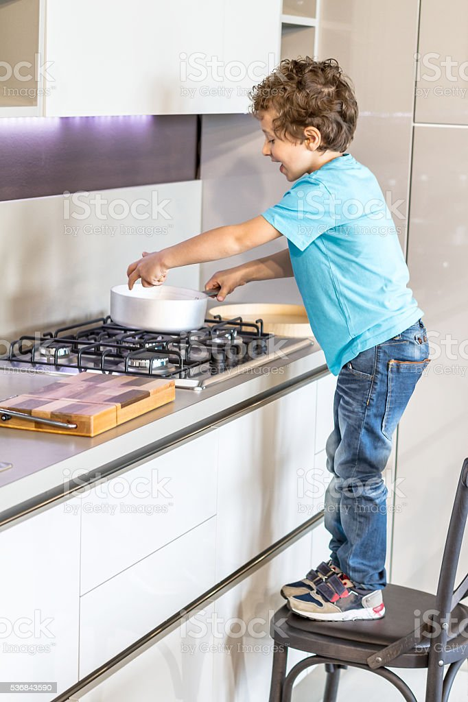 Little boy cooks using pot stock photo