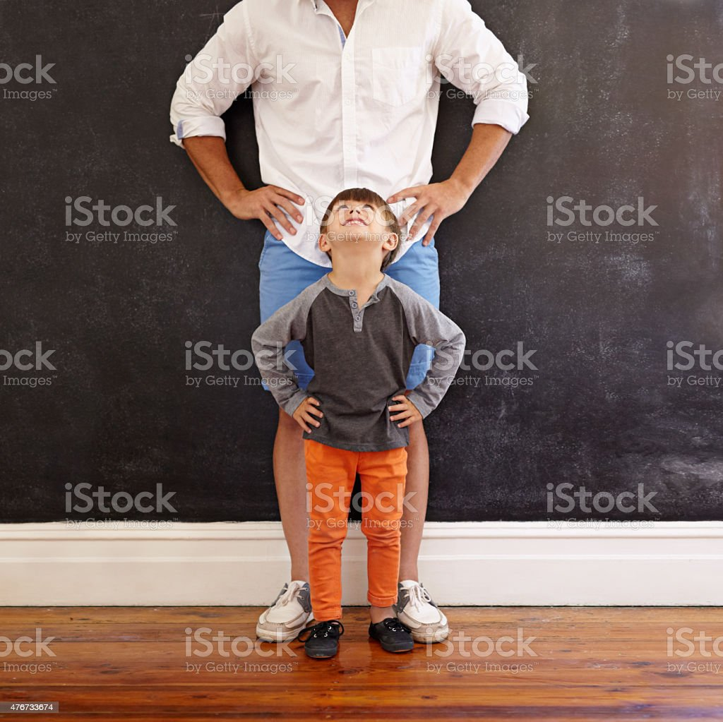 Little boy copying his father's pose stock photo