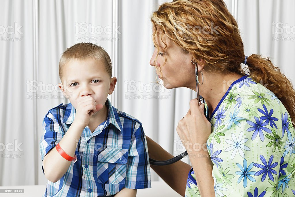 A little boy coughing while a doctor checks his lungs royalty-free stock photo