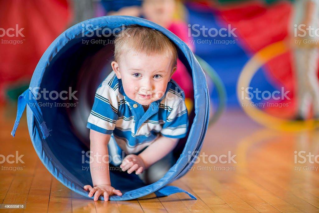 Little Boy Crawling Through Play Tunnel stock photo