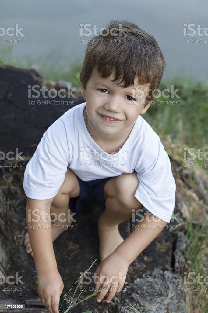 Little boy crouching at riverside royalty-free stock photo