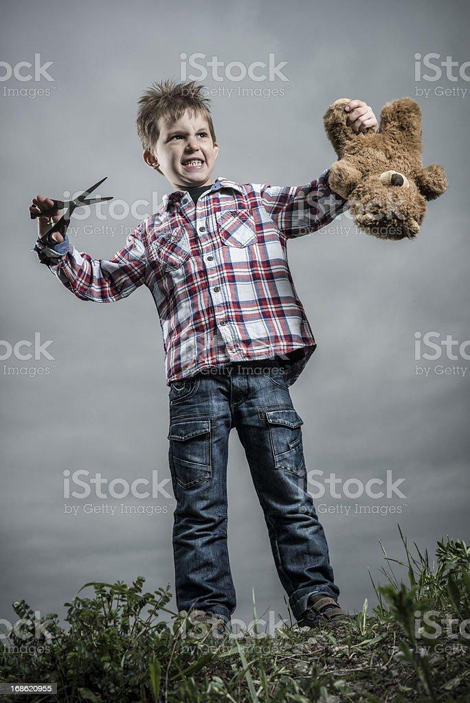 little boy cutting his teddy royalty-free stock photo