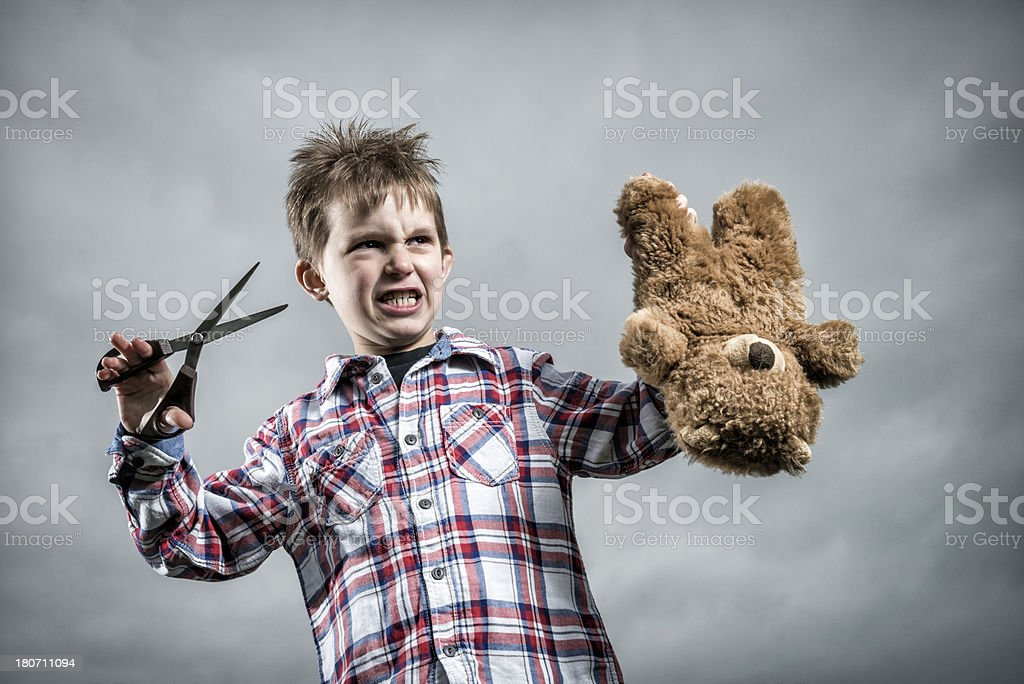 little boy cutting his teddy royalty-free stock photo