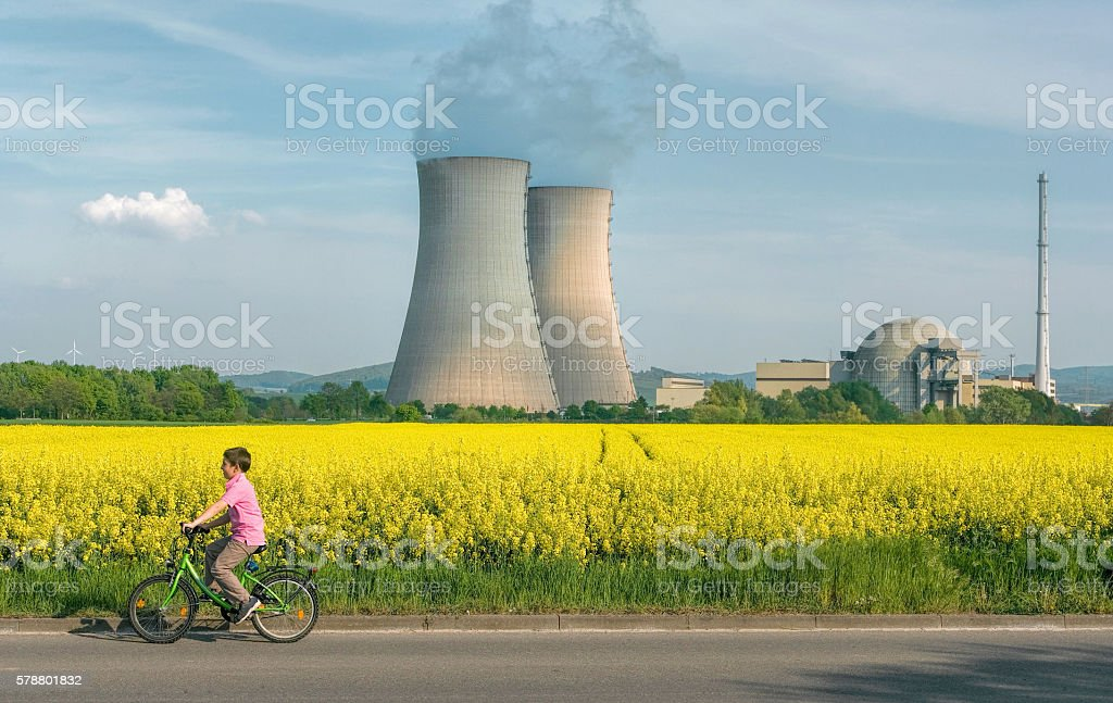 Little Boy Cycling in Front of Nuclear Power Station stock photo