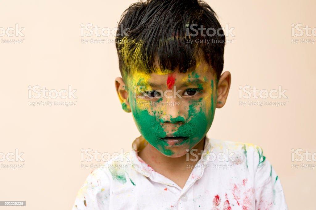 Little boy daubed in Holi colors stock photo
