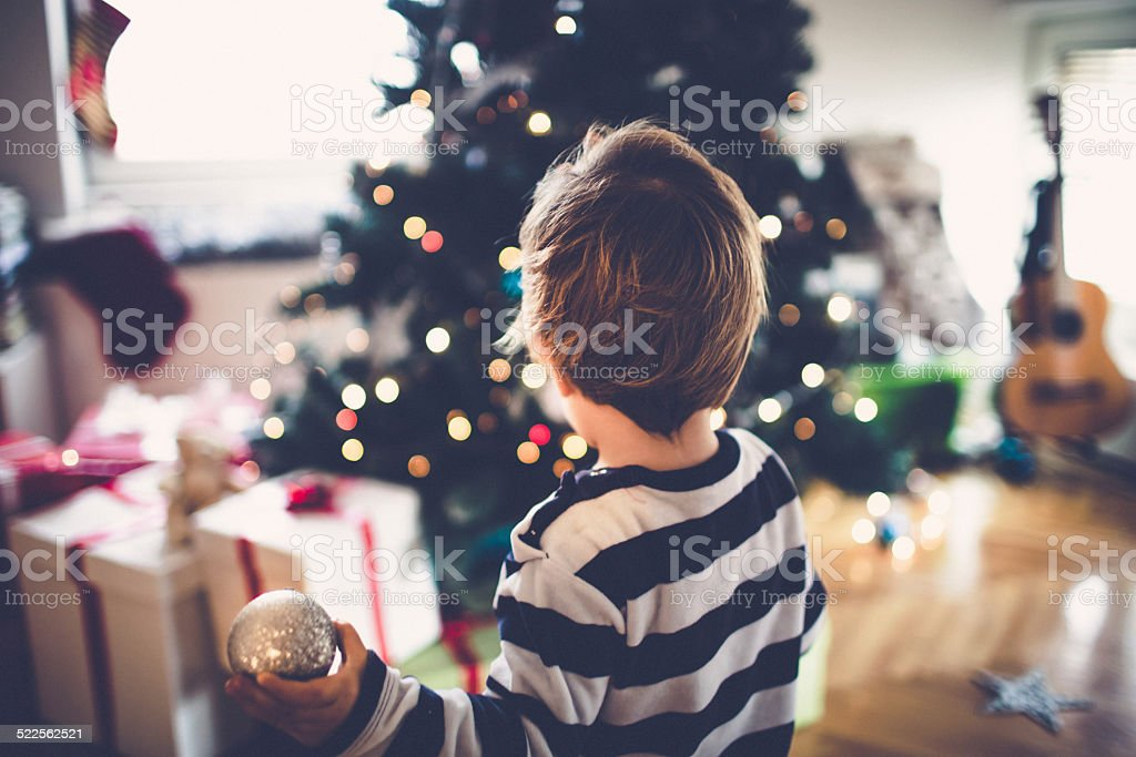 Little boy decorating his first Christmas tree stock photo